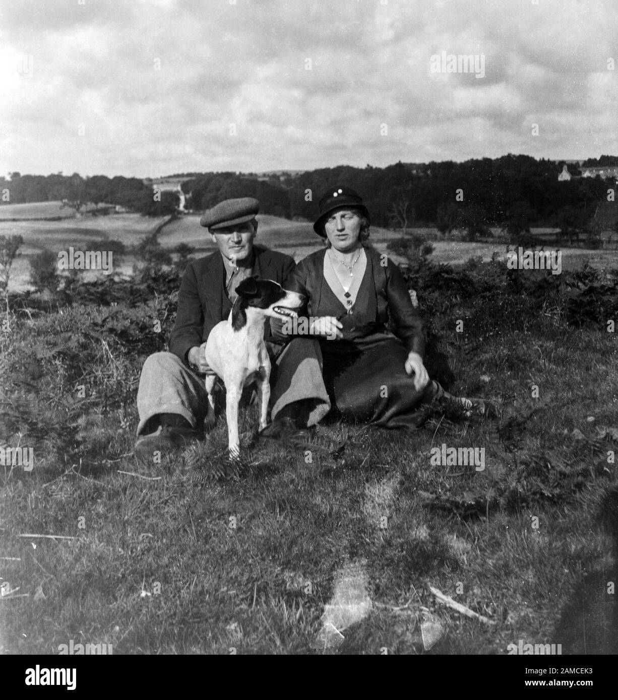 Archive image of a man and woman sitting in the countryside with their dog, circa 1920s scanned directly from the negative Stock Photo