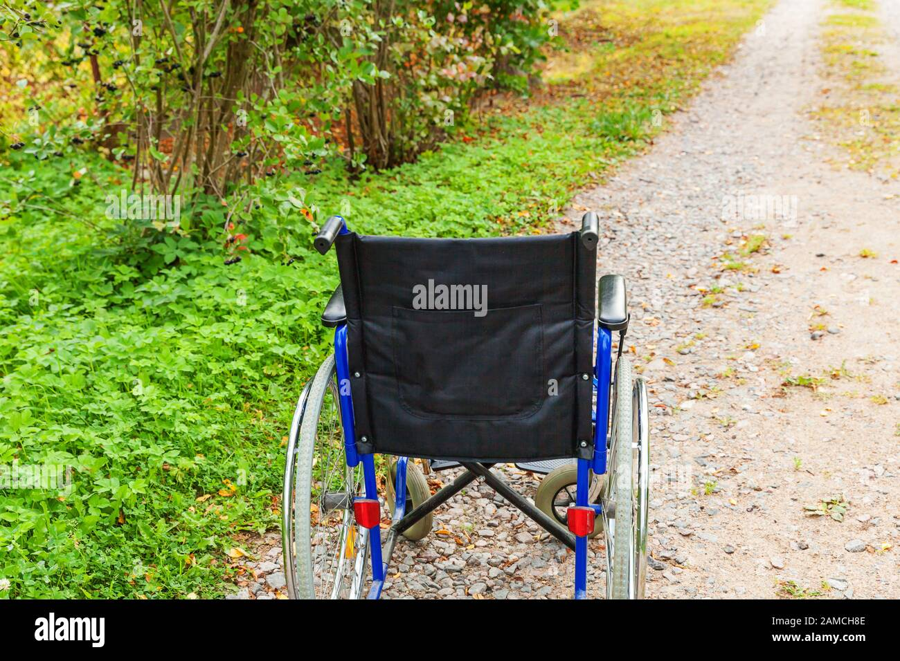 Empty wheelchair standing on road in hospital park waiting for patient services. Invalid chair for disabled people parked outdoor in nature. Handicap accessible symbol. Health care medical concept Stock Photo