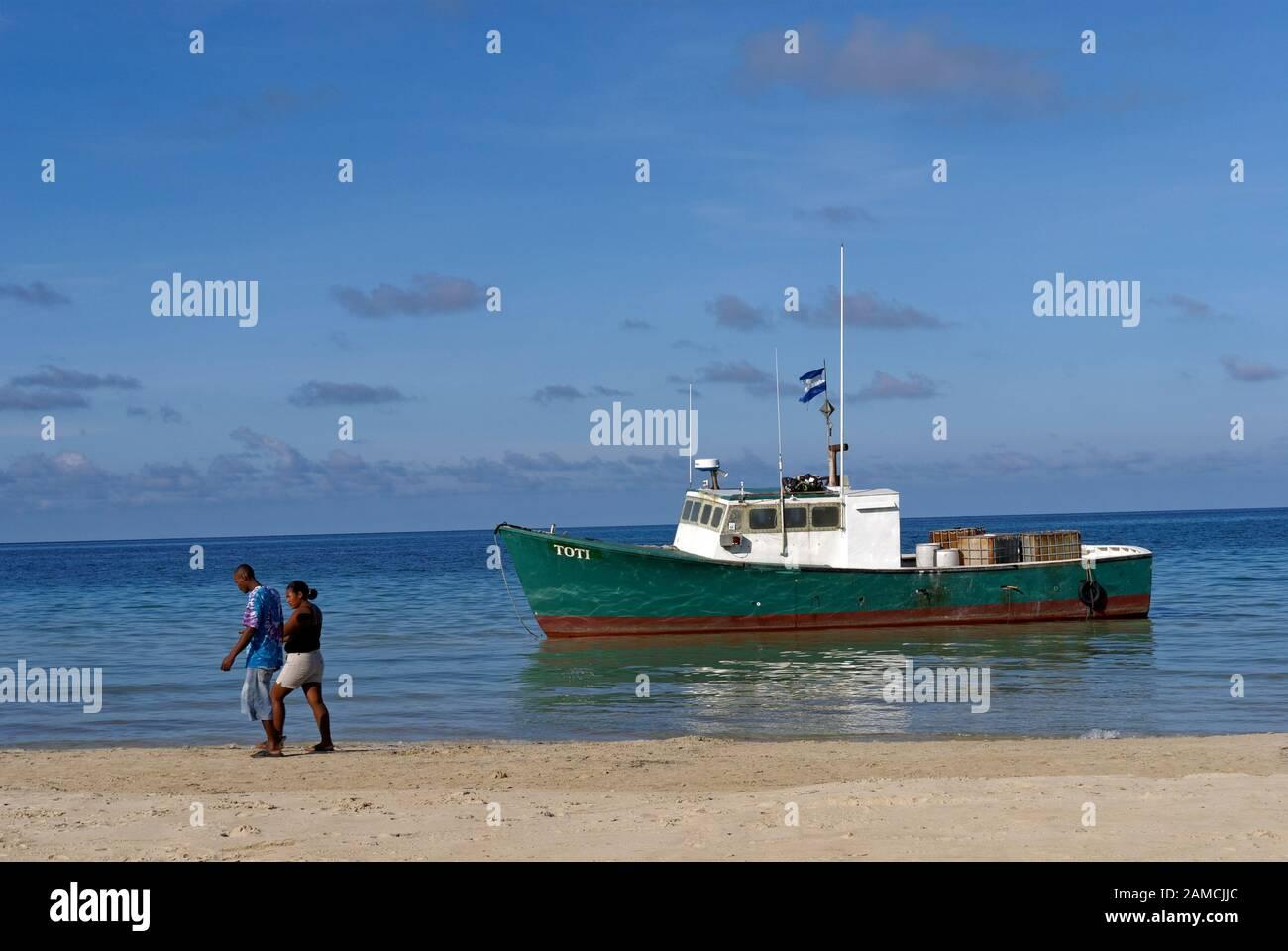 Black man and woman walking along a beach on Big Corn Island, Nicaragua, Central America Stock Photo