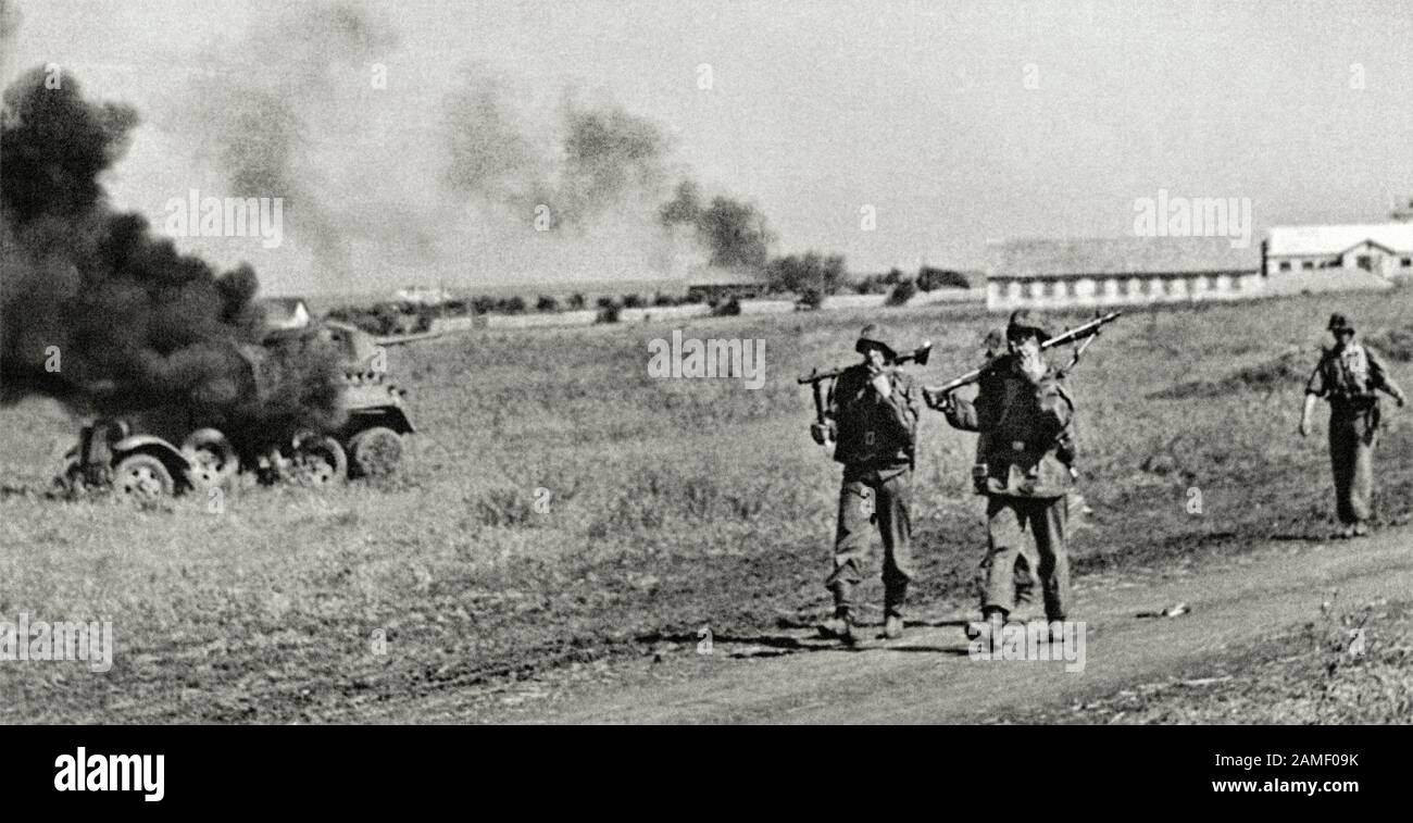 Waffen SS soldiers are walking along the road past the destroyed BA-10 Soviet armored car from the 19th tank division of the 22th mechanized corps of Stock Photo