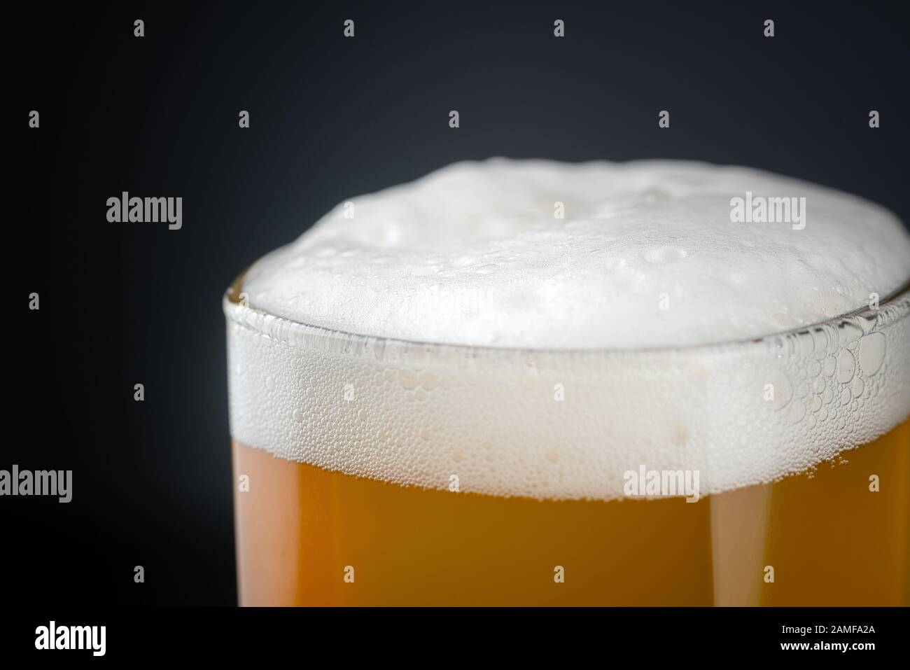 Fresh and cold glass craft beer with white foam on top on black background with space for text. Foamy wheat or lager beer on dark background Stock Photo
