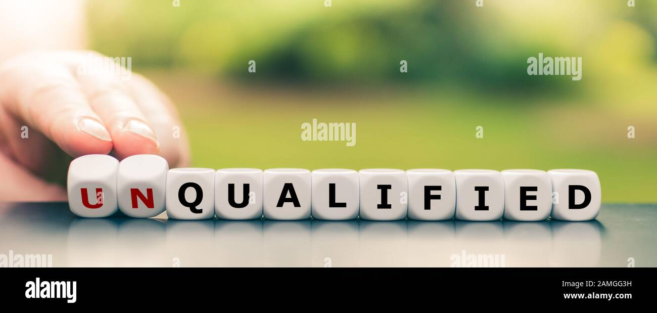 Hand turns dice and changes the word unqualified to qualified. Stock Photo