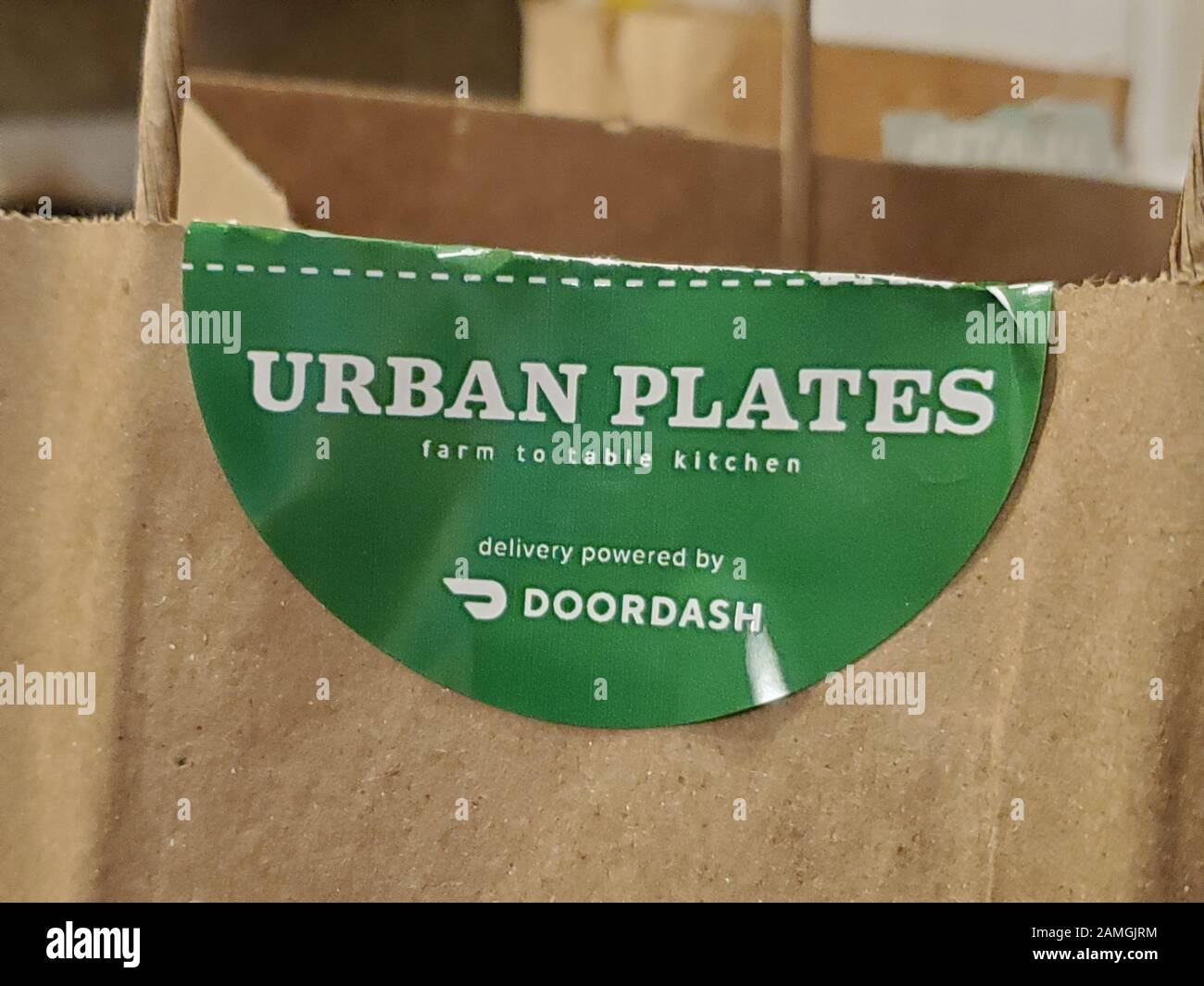 Close-up of take-out bag from restaurant Urban Plates with logo indicating that delivery for the restaurant is accomplished via the gig economy company Doordash, San Ramon, California, December 11, 2019. Despite fees, many restaurants are partnering with gig economy companies to offer delivery to their customers. () Stock Photo