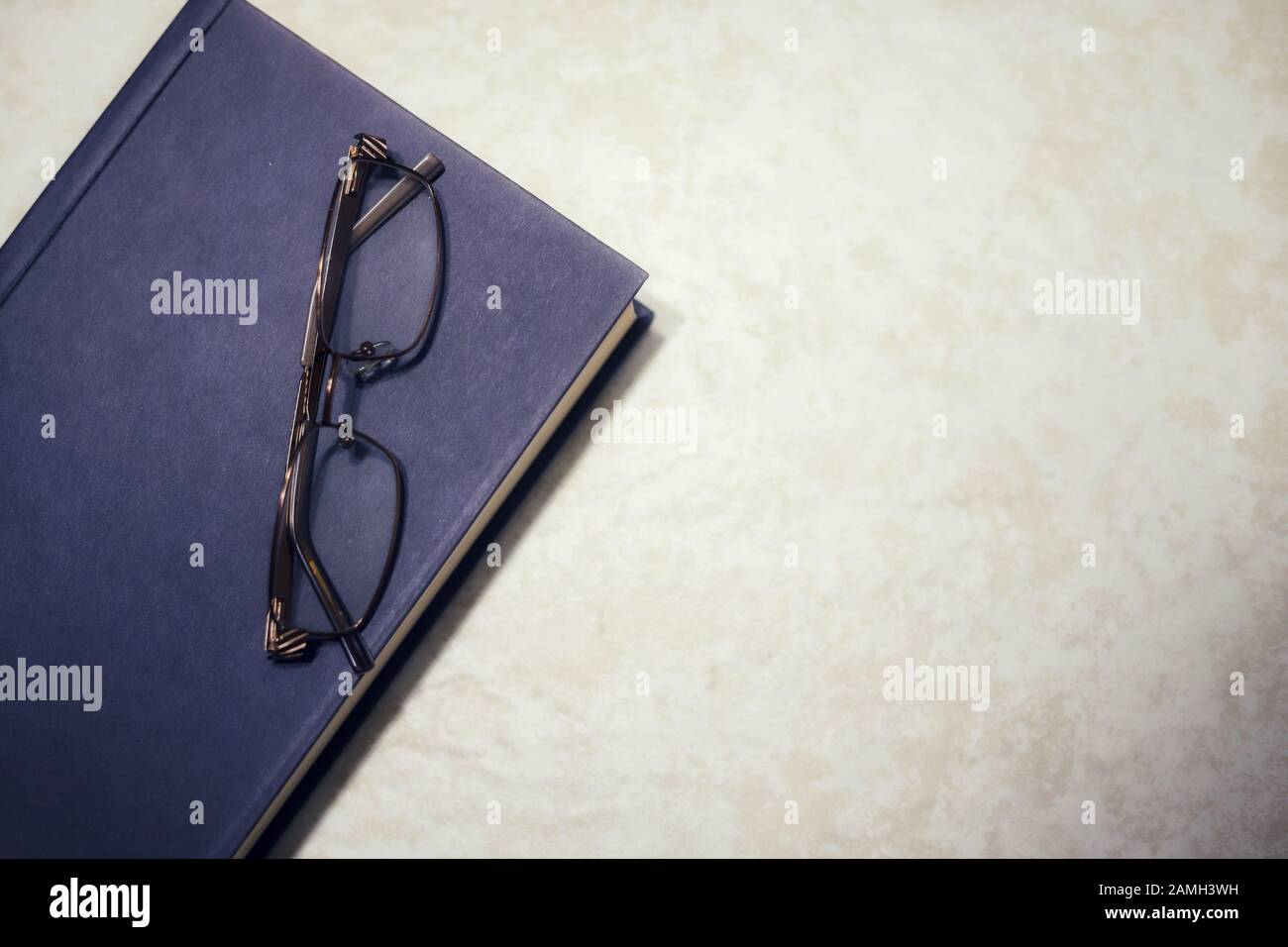 A blue hardcover book with a pair of reading glasses on top with copy space Stock Photo