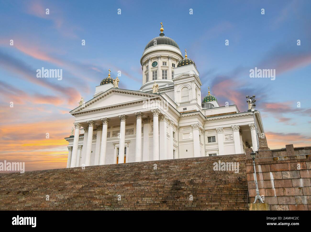 The neoclassical Helsinki Cathedral and the steps leading up to it from the Senate Square under a colorful sunset sky in Helsinki Finland. Stock Photo