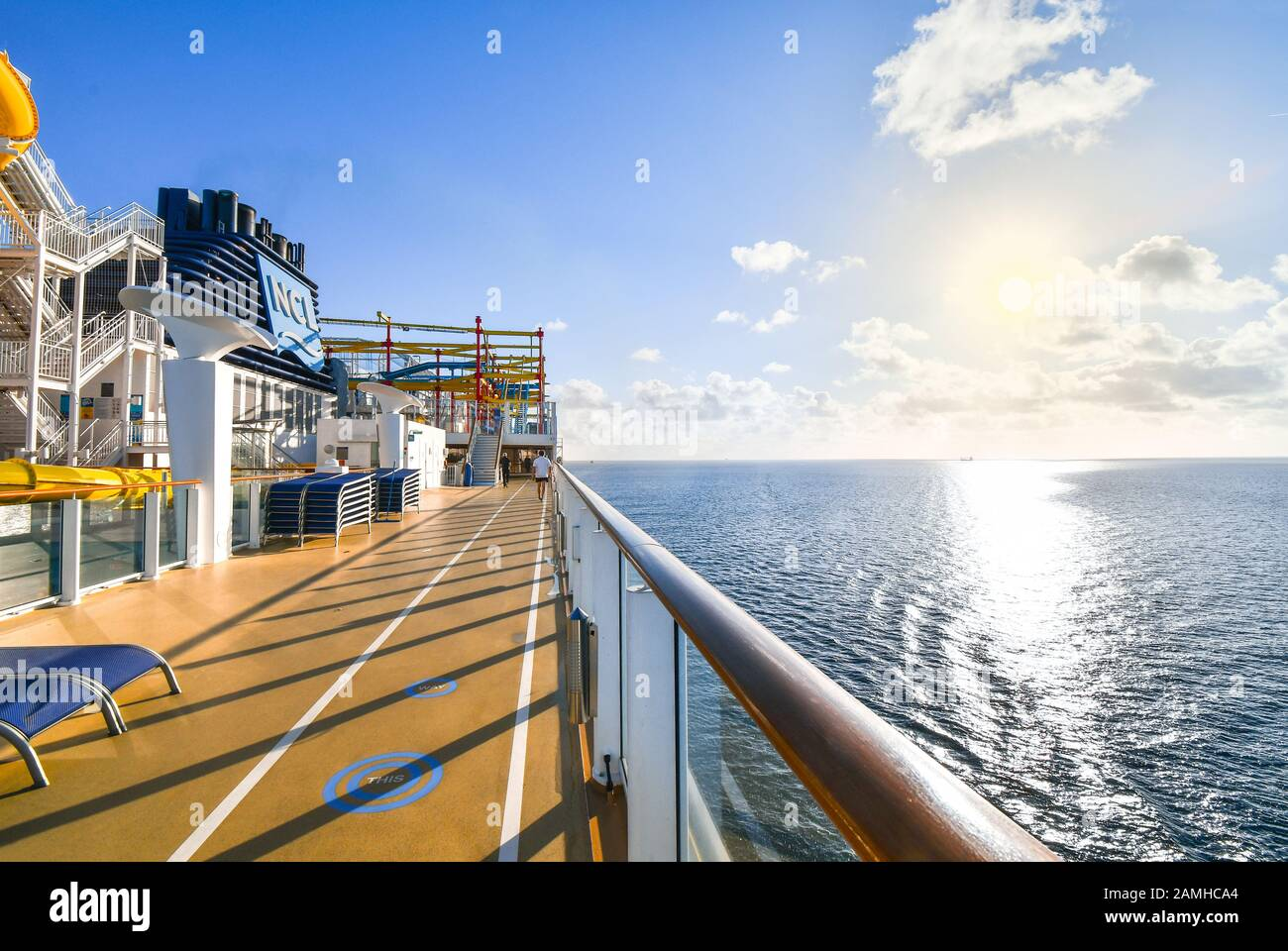 A cruise passenger uses the upper deck jogging and walking path on a luxury cruise liner with a ship in the distance on the Baltic Sea. Stock Photo