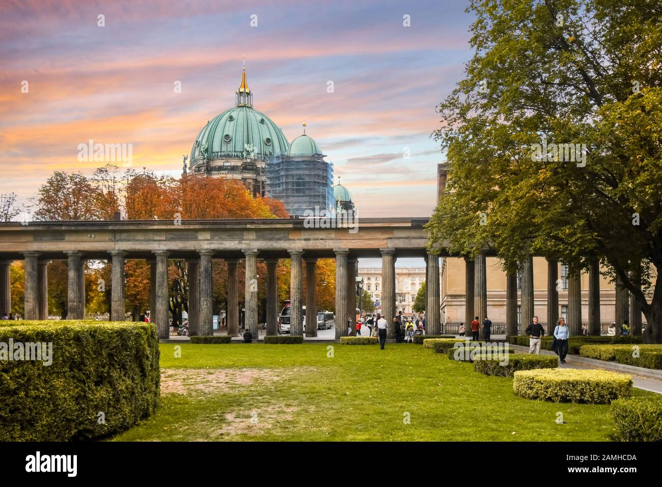 Tourists and local Germans enjoy an autumn day under a colorful sky on Museum Island with the  Berlin Cathedral in view as leaves turn orange. Stock Photo