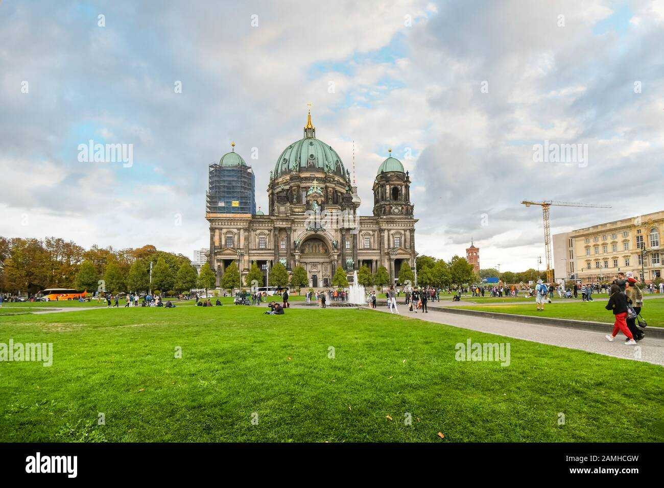 The front facade of the Berlin Cathedral as the public gather in the Lustgarten park on a partly cloudy day in late summer. Stock Photo