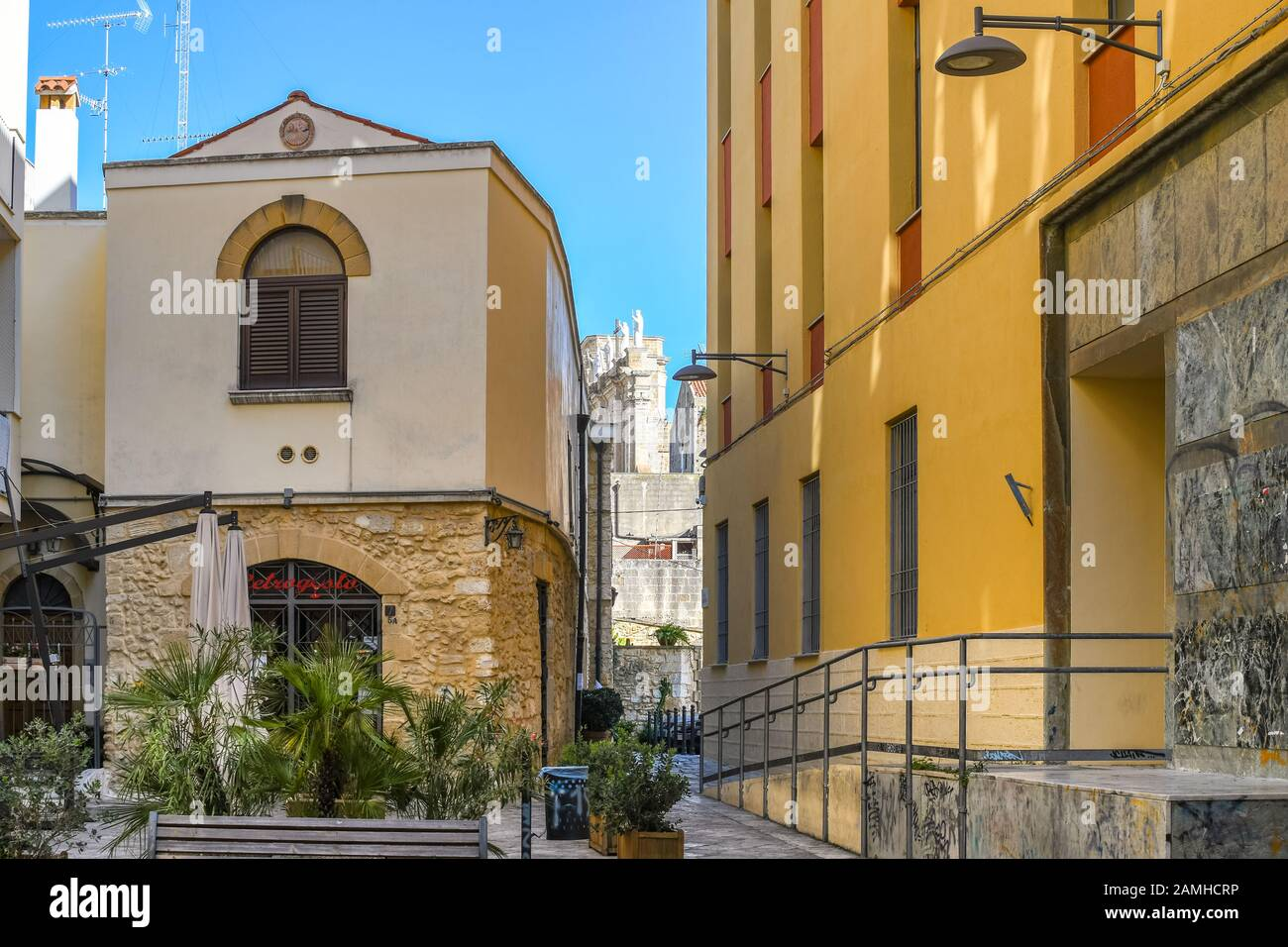 A small courtyard in the tourist center of Brindisi Italy with the Brindisi Cathedral Duomo statues visible behind on a sunny day in the Puglia Region. Stock Photo