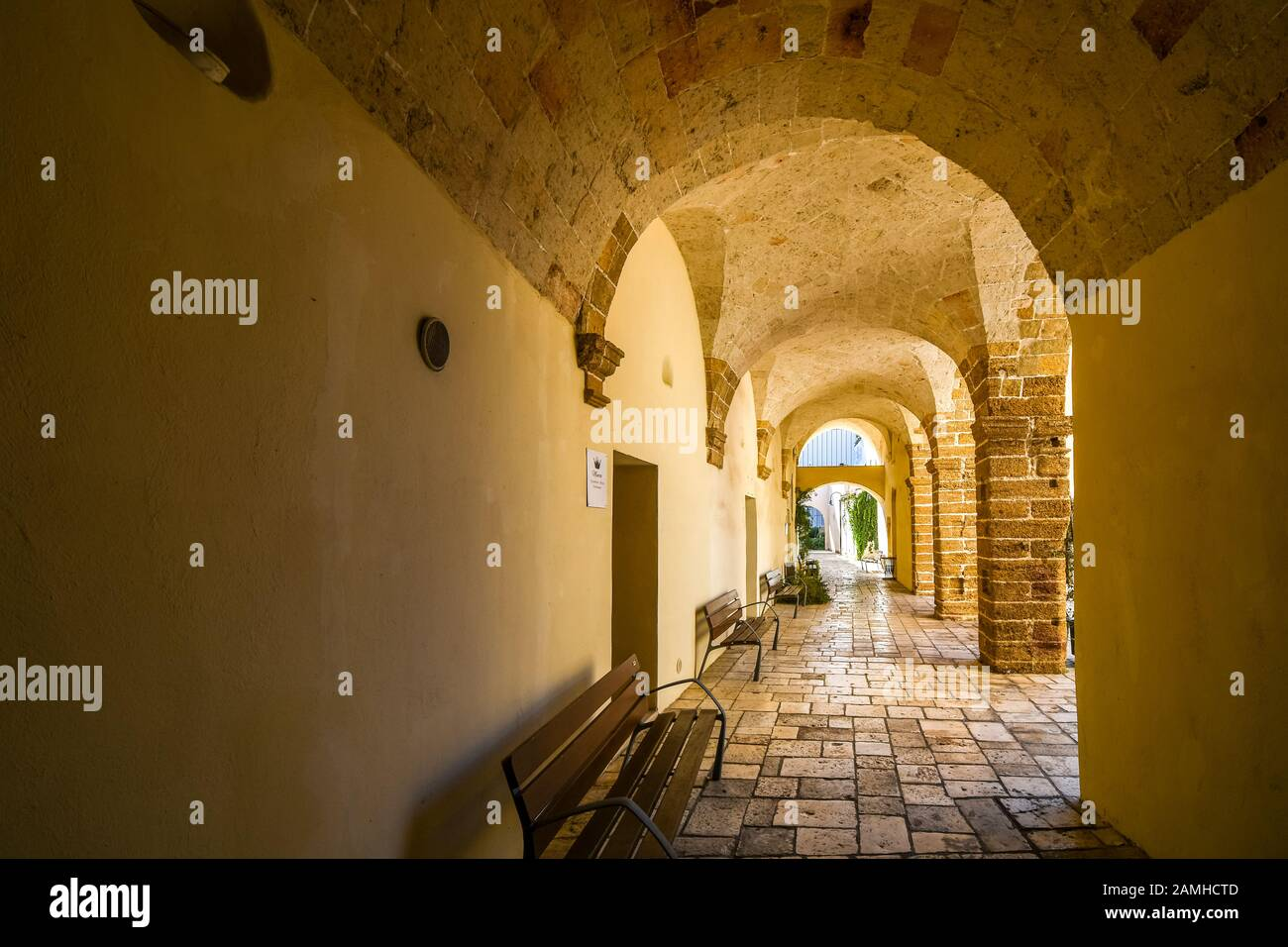 A long, covered and arched portico hallway in the historic center of Brindisi, Italy, on the coast of the Adriatic Sea in the Puglia region. Stock Photo
