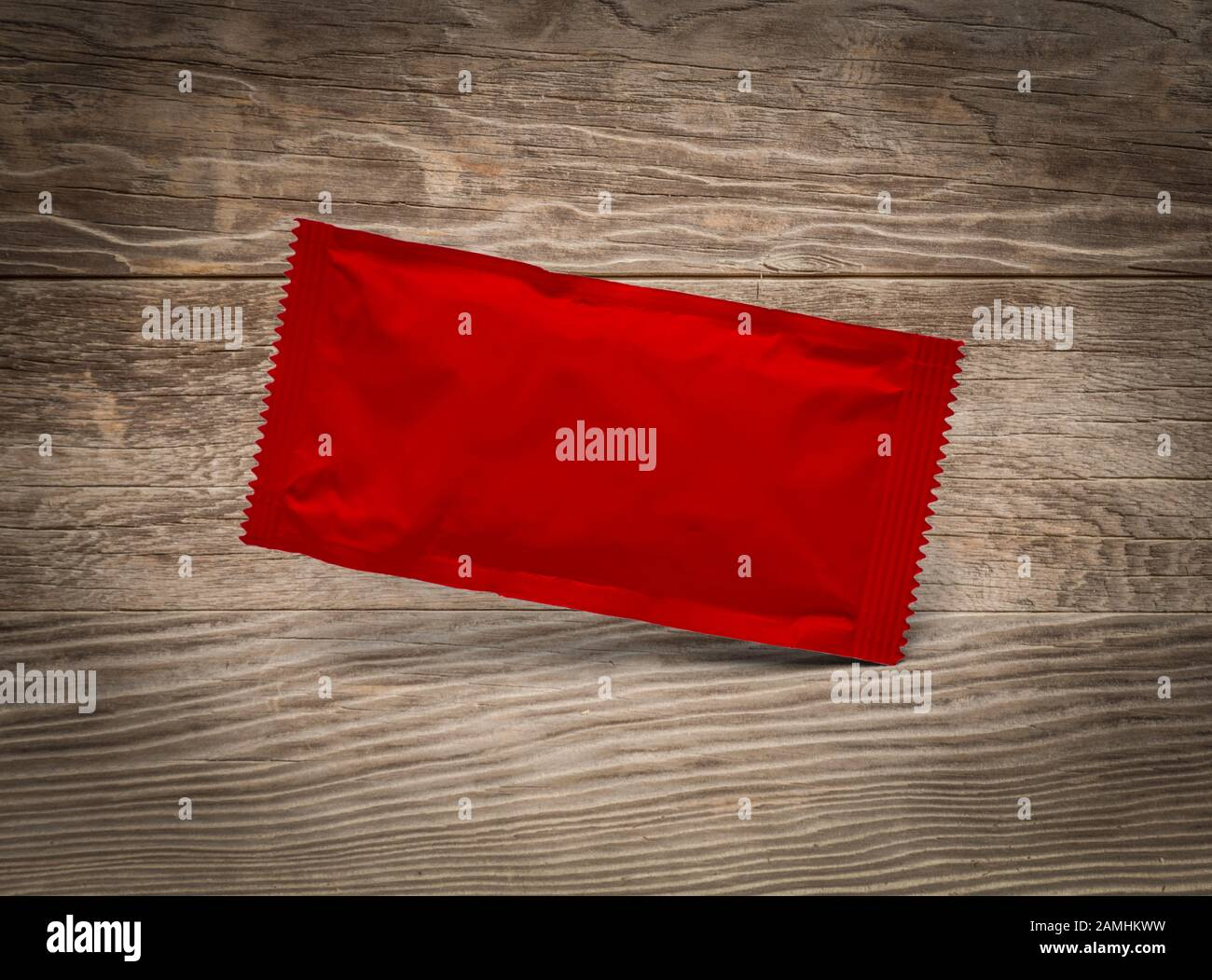 Blank Red Condiment Packet Floating on Aged Wood Background. Stock Photo