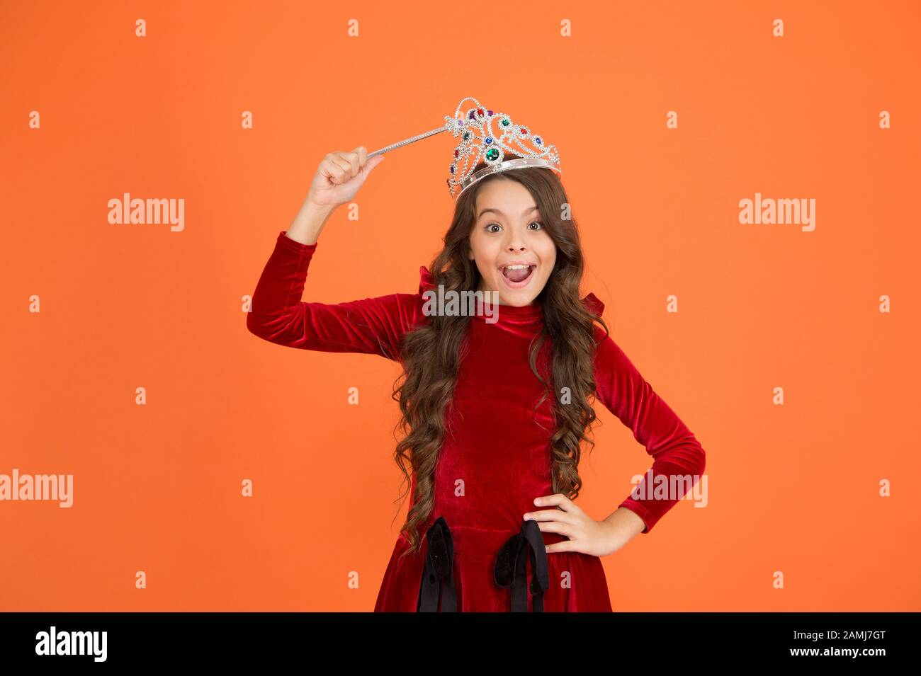 Indulge yourself in Luxury. royal and luxury. happy girl long curly hair in crown. little princess hold magic wand. magic queen from fairytale. just make a wish. all dreams come true. airs and graces. Stock Photo