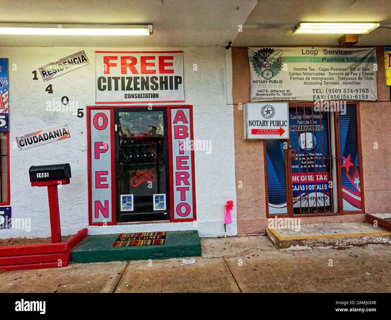Brownsville, TX, USA-30Dec2019-Across from the bus station, stores serve the needs of residents and visitors along the border between Mexico and the United States. Free Citizenship in large letters, underneath it simply says counseling. Bilingual signs in Spanish and English Stock Photo