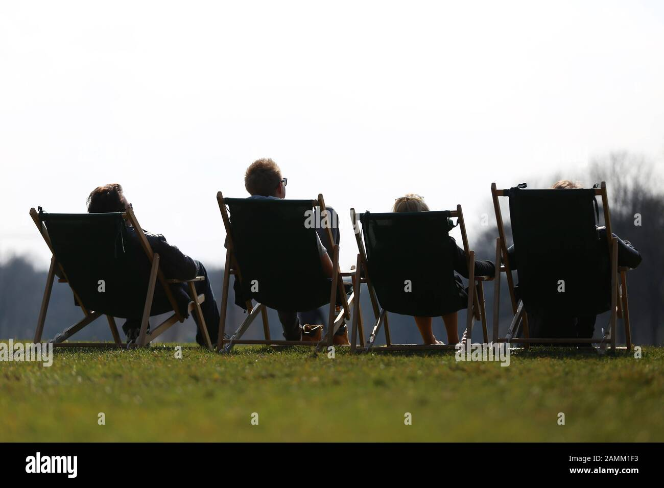 Spectators in deck chairs in the English Garden watch the partial solar eclipse over Munich. [automated translation] Stock Photo