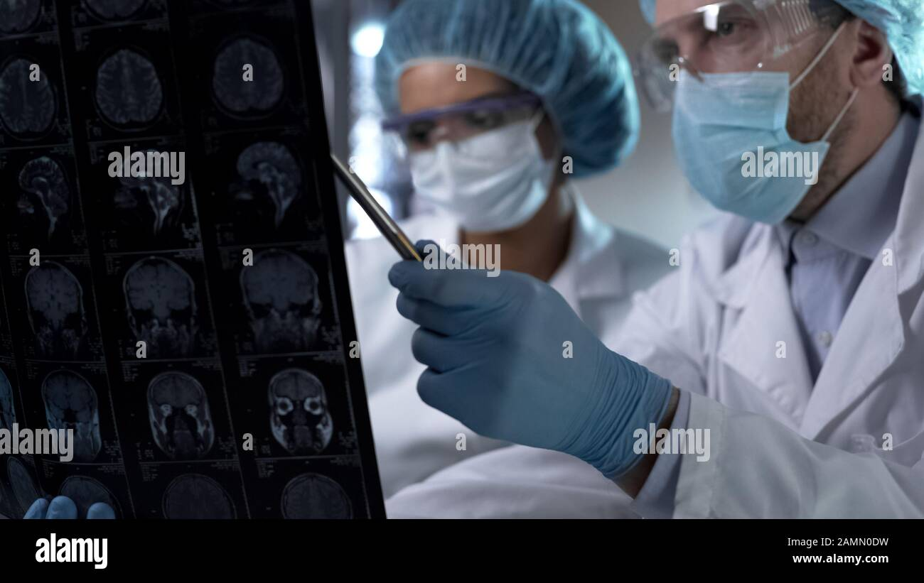 Neurosurgeon showing human MRI scan and giving explanation to medical intern Stock Photo