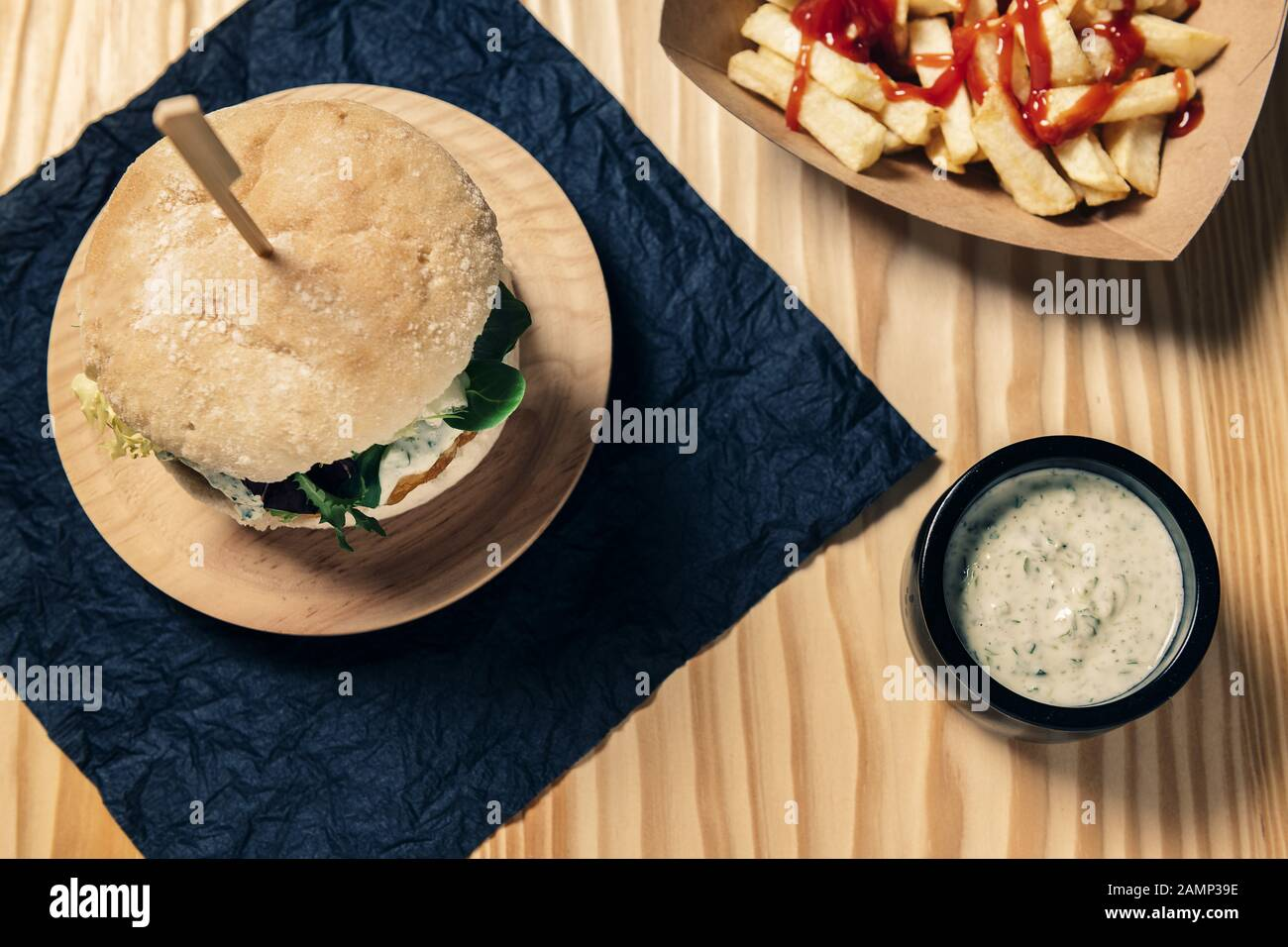 top view of a gourmet vegan burger on a wooden table with french fries with ketchup in a cardboard tray and a jar with sauce, healthy food and foodie Stock Photo