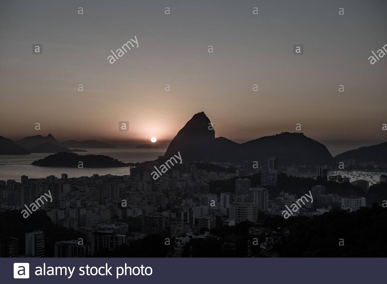 The skyline of Sugarloaf Mountain and Botafogo in Rio de Janeiro, Brazil in the early morning at sunrise. Seen from Santa Teresa Stock Photo