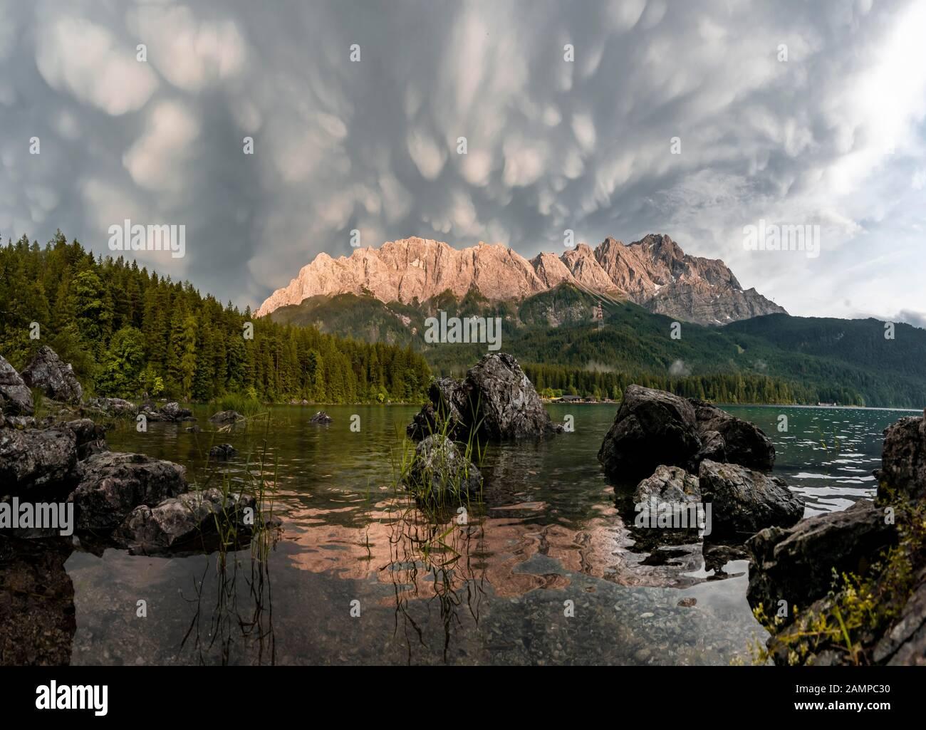 Rocks on the shore, Eibsee lake in front of Zugspitze massif with Zugspitze, sunset, dramatic Mammaten clouds, Wetterstein range, near Grainau, Upper Stock Photo