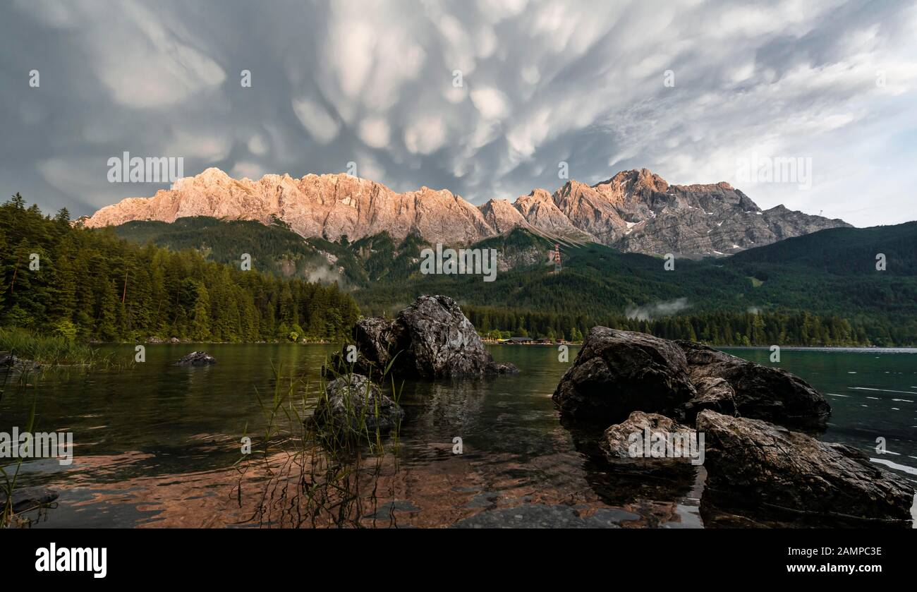 Rocks on the shore, Eibsee lake in front of Zugspitze massif with Zugspitze, sunset, dramatic Mammaten clouds, Wetterstein range, near Grainau, Upper Stock Photo