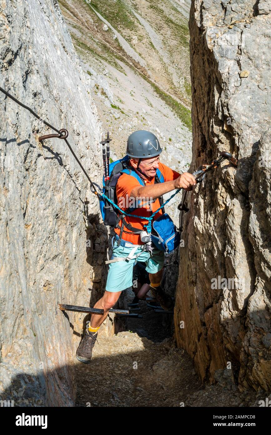 Mountaineer, man with climbing helmet on a secured fixed rope route, Mittenwald via ferrata, Karwendel Mountains, Mittenwald, Germany Stock Photo