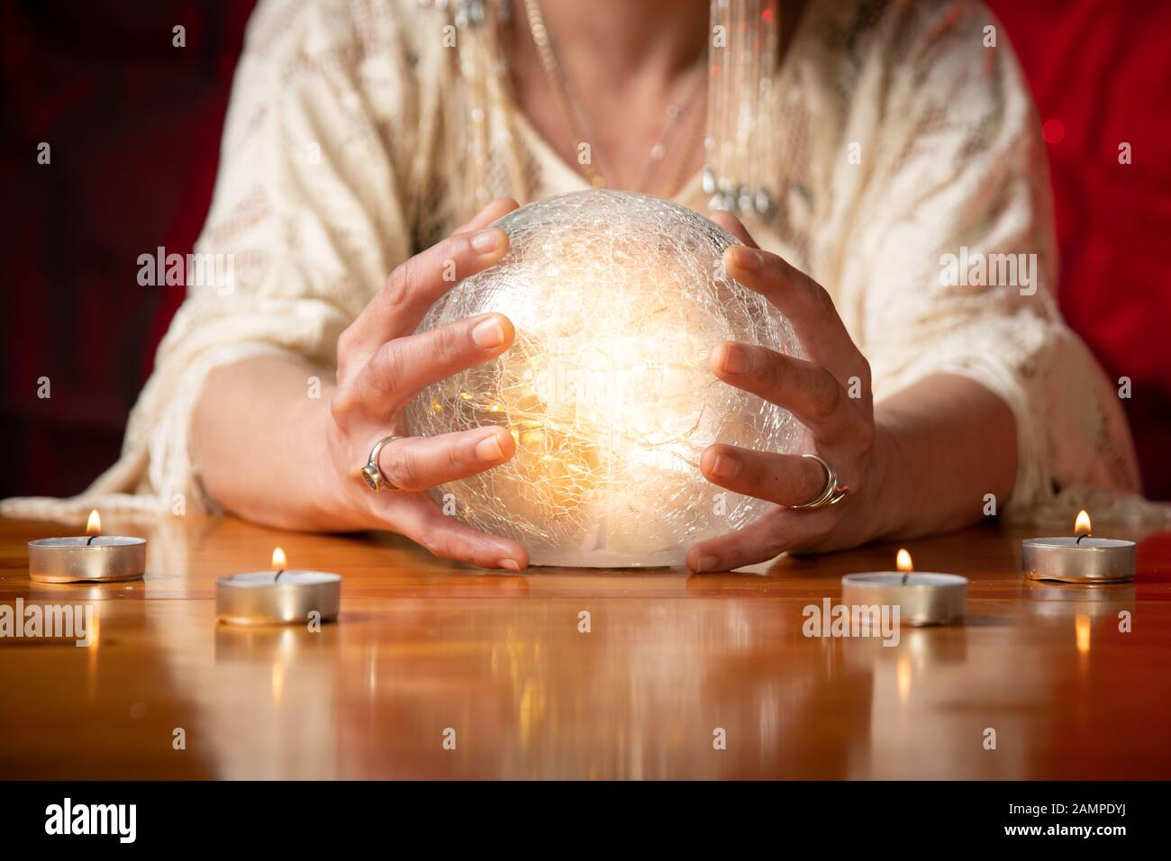 Fortune Teller with Crystal Ball on table with candles and black and red mottled background Stock Photo