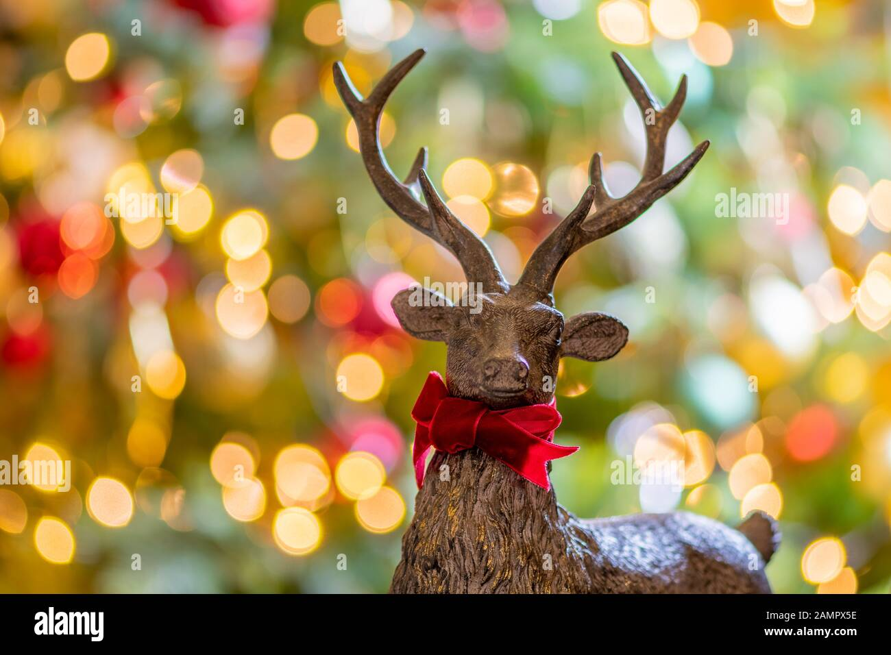 Close up of a wooden deer shaped christmas decoration with defocused fairy lights in the background Stock Photo