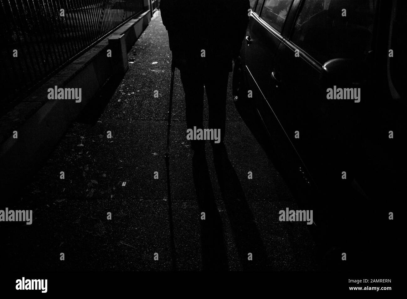 Black and white scene of Silhouette of senior man walking on French street using walking stick preserving equilibrium with blue ane Medical assistance and rehabilitation Stock Photo
