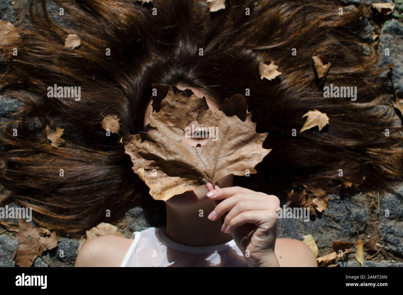 Teenage girl lying on floor with leaves in her hair Stock Photo