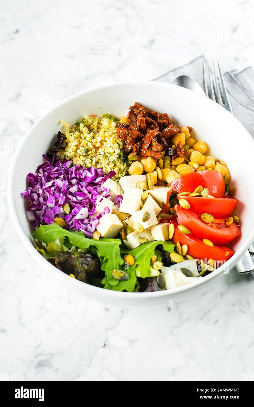 Vegetarian buddha bowl. Raw vegetables, tofu and bulgur in white bowl. Vegetarian, healthy, detox food concept Stock Photo