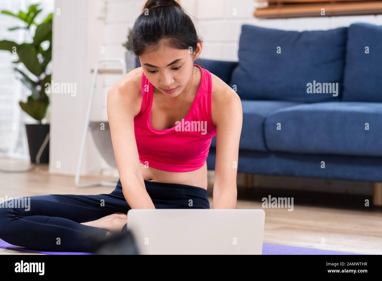 Asian Woman In Sportswear Sitting On Matt In Living Room And Training Yoga Exercises Online Video Tutorial On Laptop Stock Photo Alamy