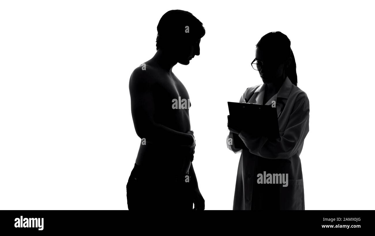 Silhouette of man at medical examination, female doctor writing prescription Stock Photo