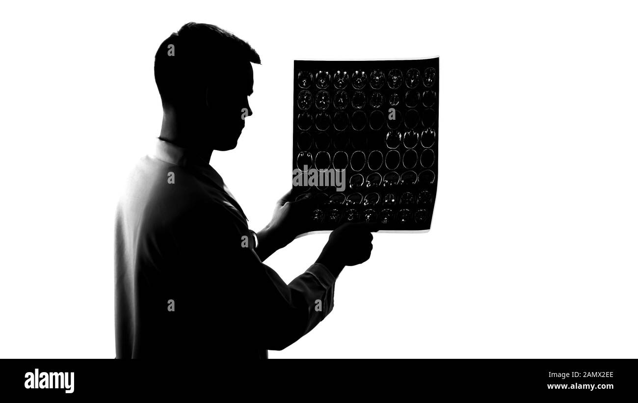 Silhouette of young neurologist examining mri results, brain disease, occupation Stock Photo