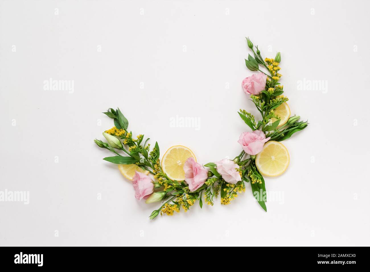 Creative arrangement of pink and yellow flowers with lemons on a white background with a copy space Stock Photo