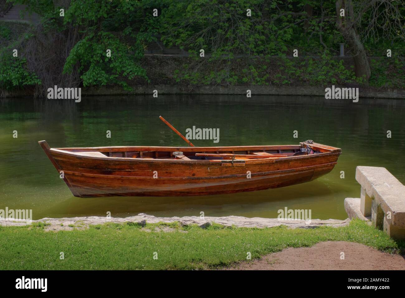 Wooden boat standing near river bank in park, solitude and calmness, relaxation Stock Photo