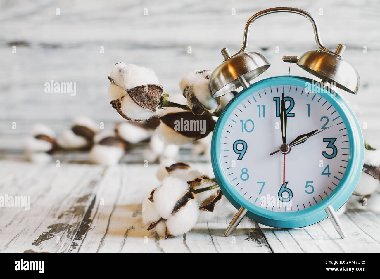 Set your clocks back with this clock iand bolt of cotton over a white wooden table. Daylight saving time concept. Selective focus with blurred backgro Stock Photo