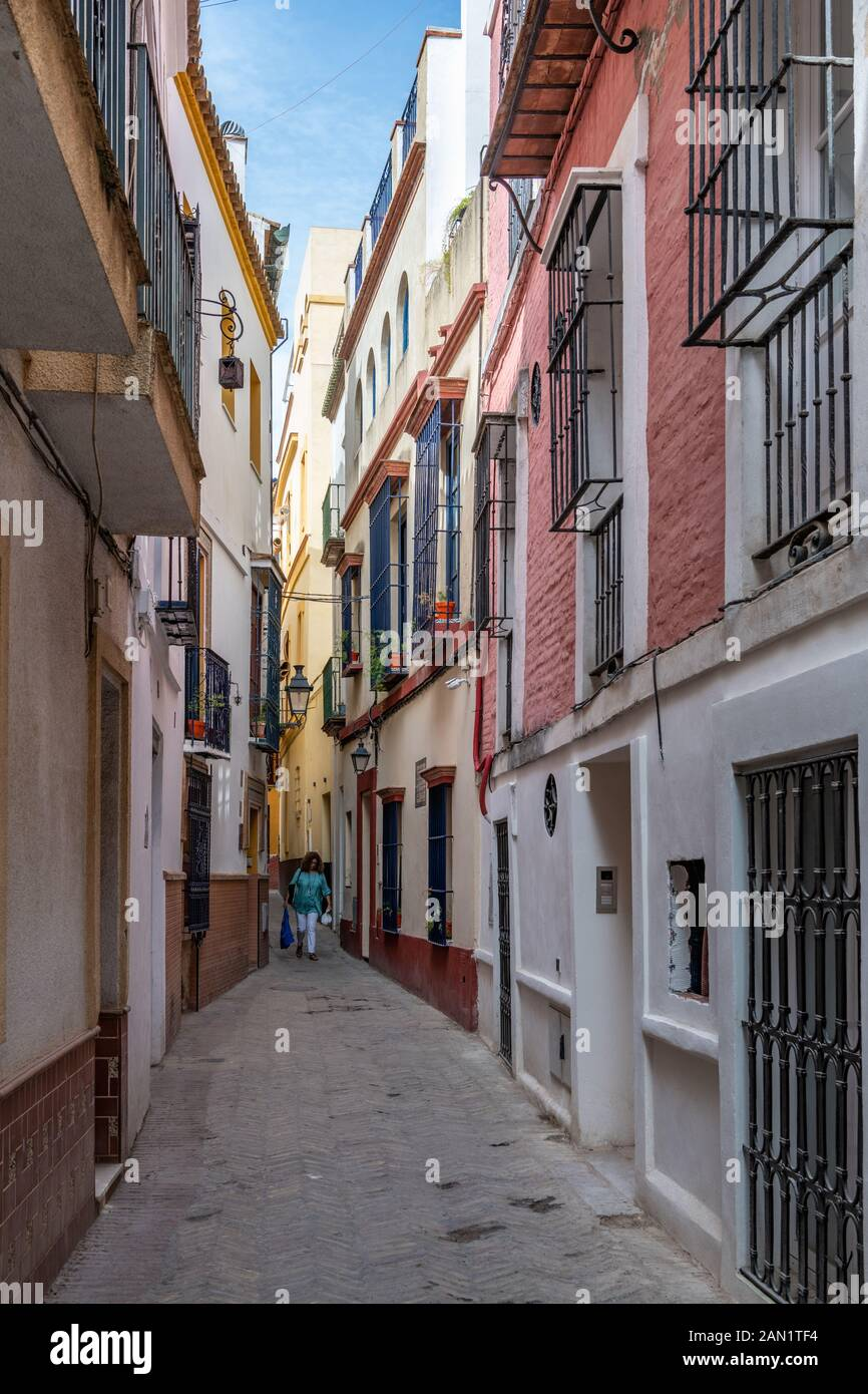 Colourful buildings line a narrow alley in Seville's historic Jewish Quarter. Stock Photo