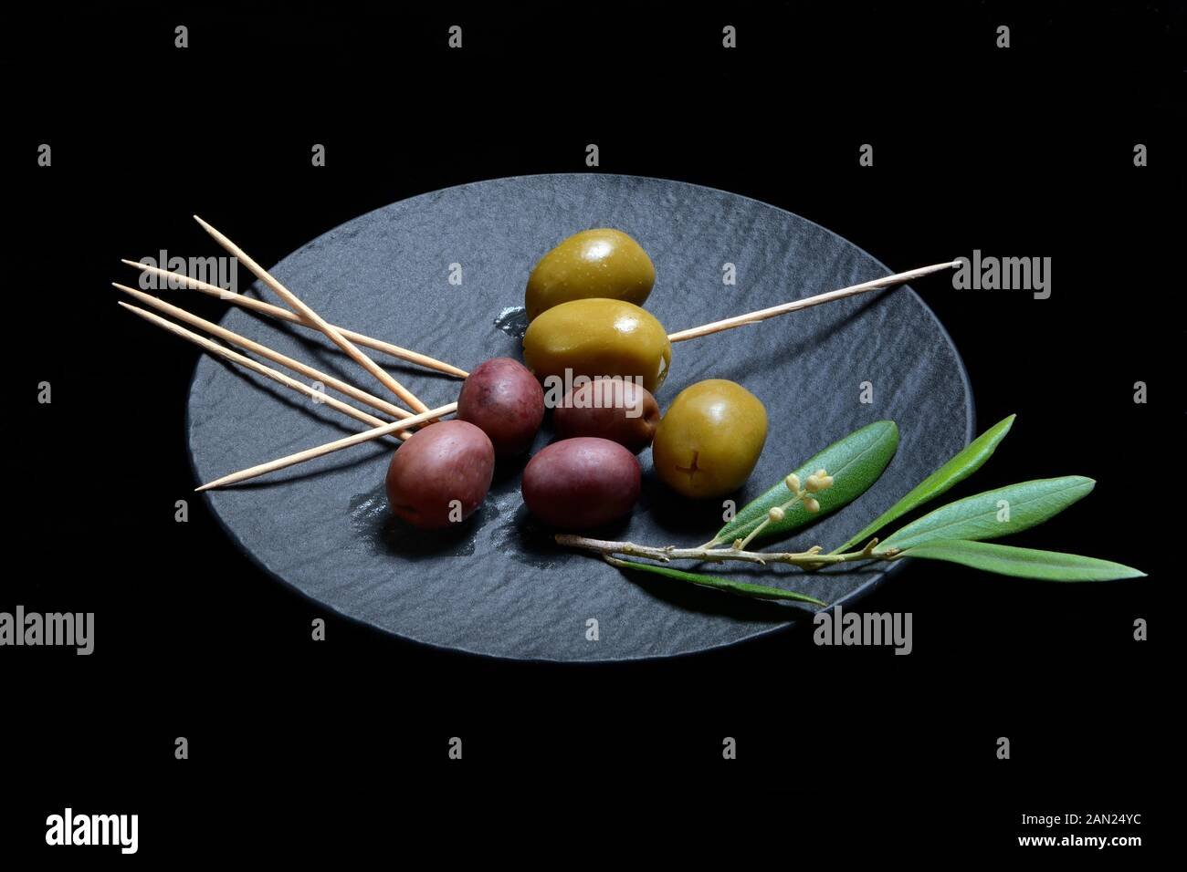 Black and green olives with toothpick on black plate, Germany Stock Photo