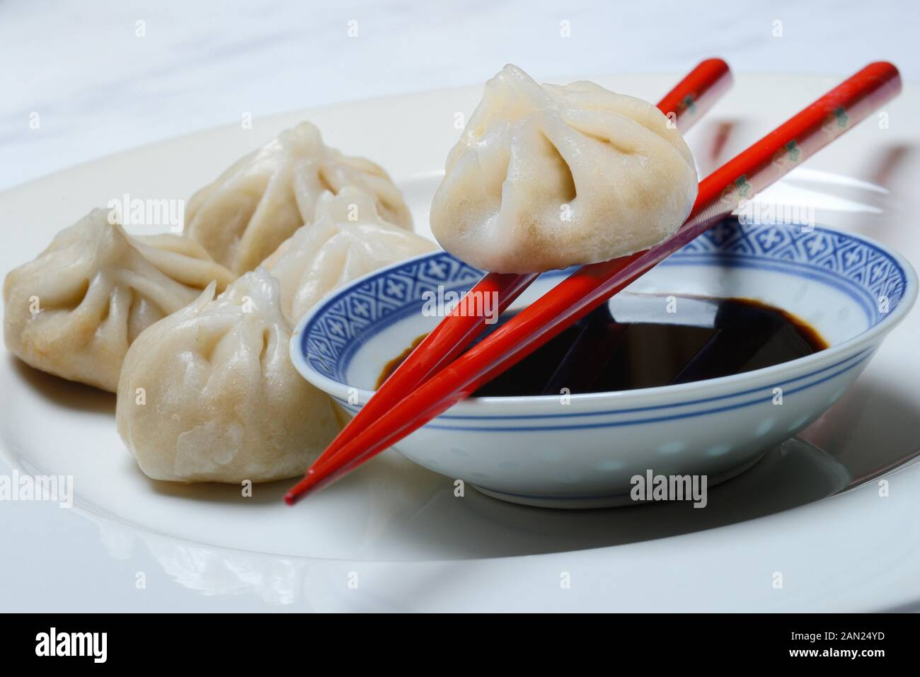 Dim Sum, filled dumplings and bowl with soy sauce, red chopsticks, Germany Stock Photo