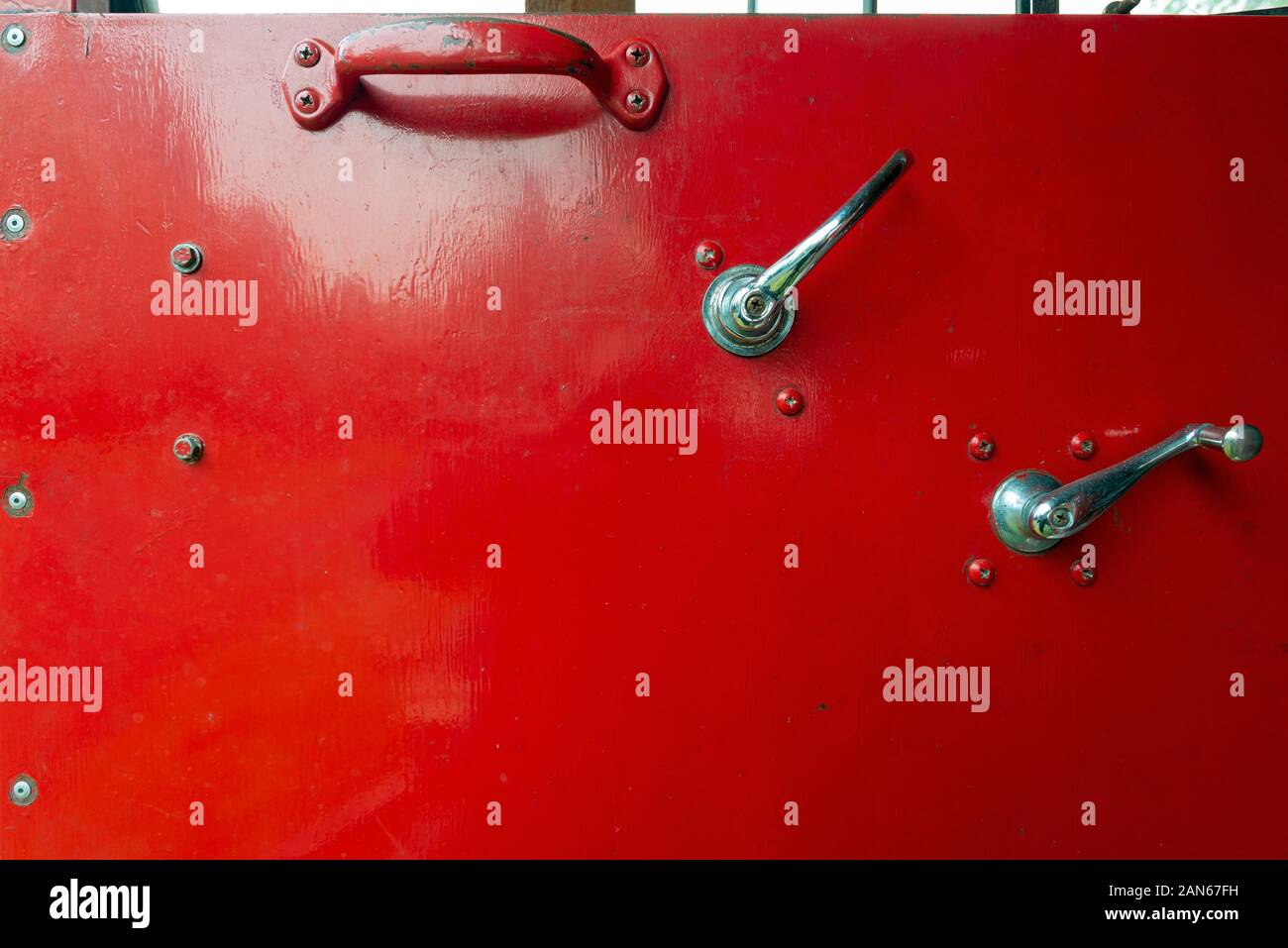 A Red Metal Door of an Old Fire Truck with Window Crank and Handles Stock Photo
