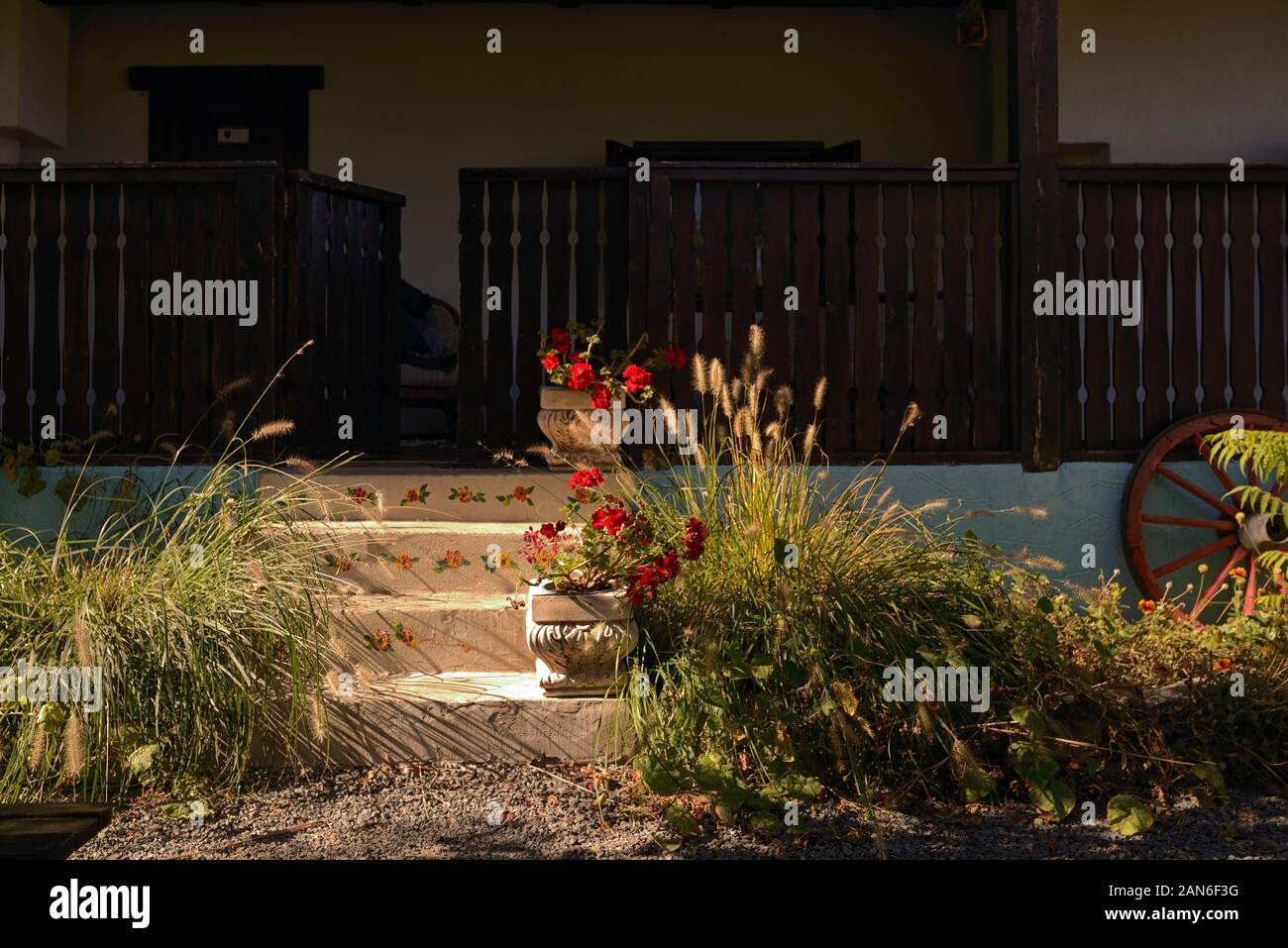 Old Style Rustic House With Laborious Wood Porch Stock Photo