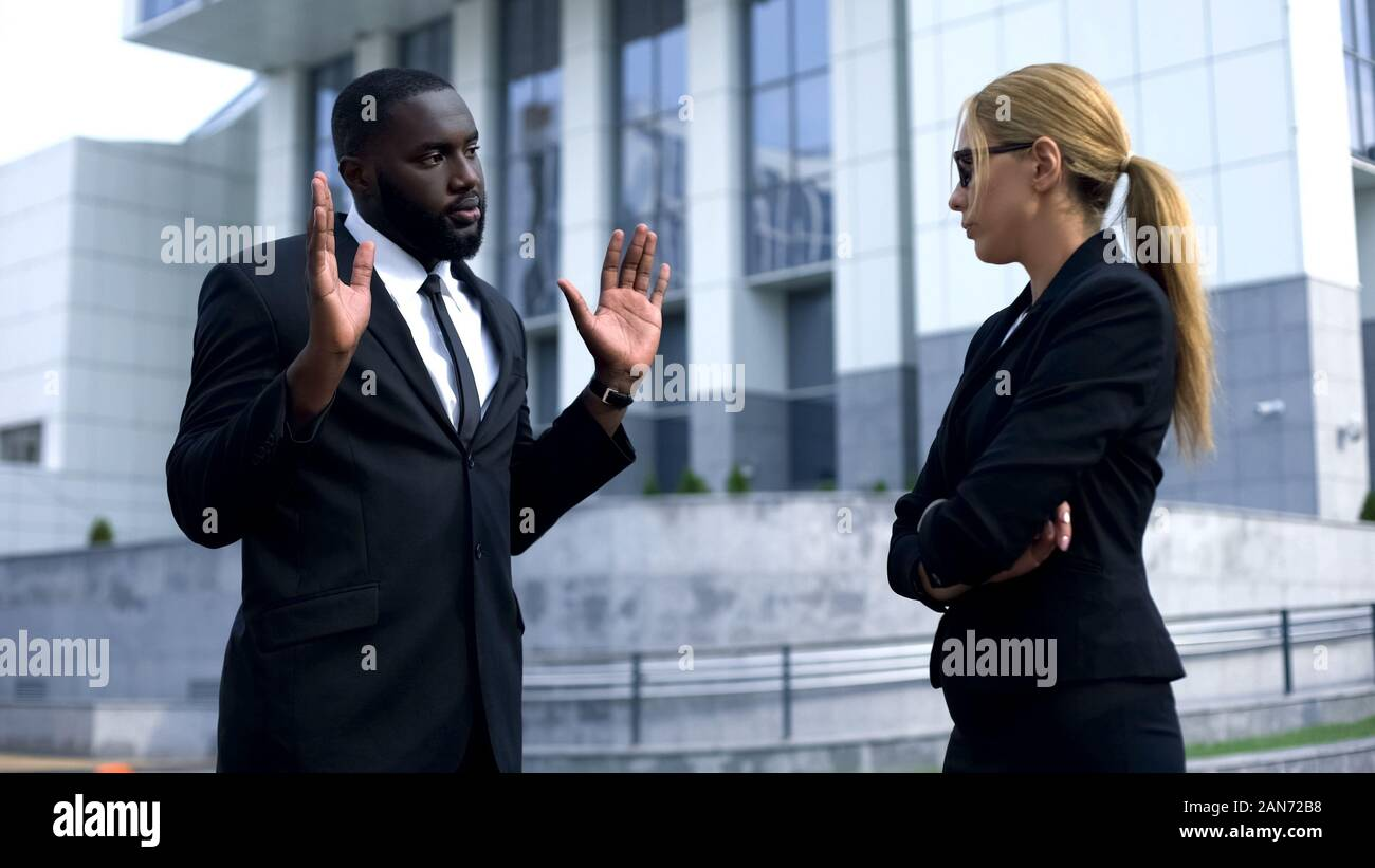 Female boss offending afro-american employee, man trying to justify his doings Stock Photo