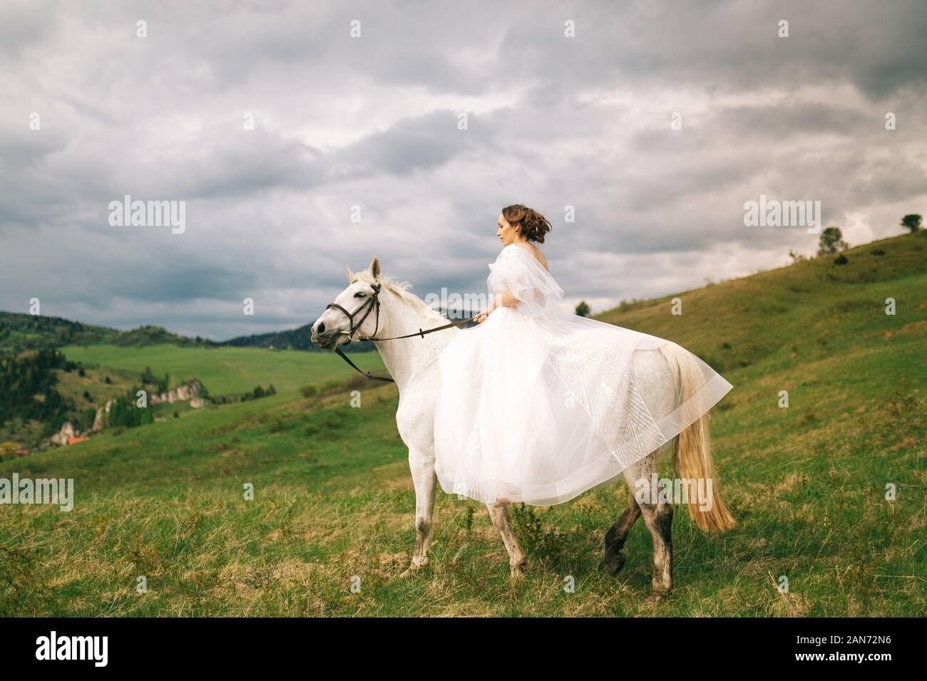 Bride In Wedding Dress Rides A White Horse Stock Photo Alamy