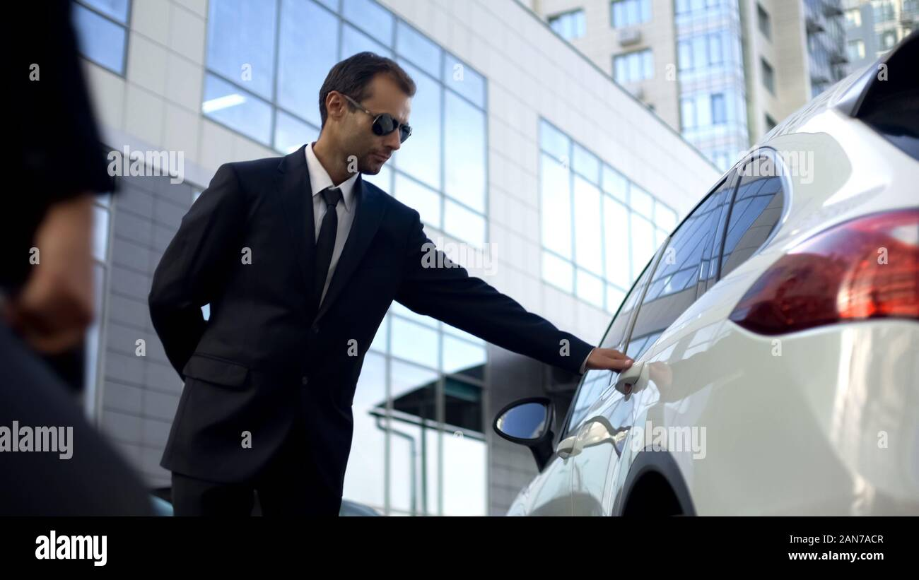 Personal driver meeting and opening car door for lady boss, bodyguard  duties Stock Photo - Alamy