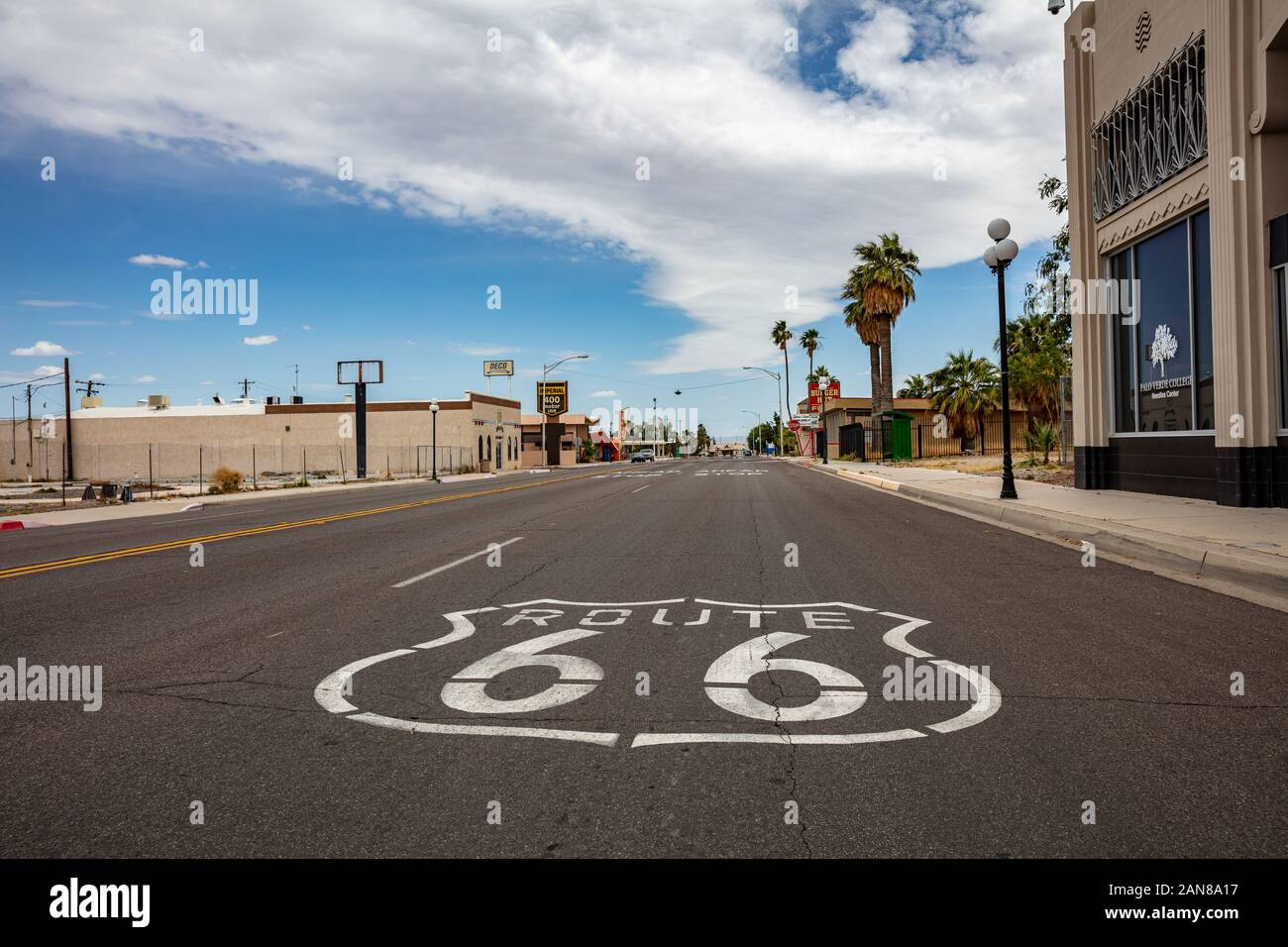 Needles, California, USA. May 26, 2019. Route 66 historic mother road sign on the asphalt street, empty road, cloudy blue sky background. Stock Photo