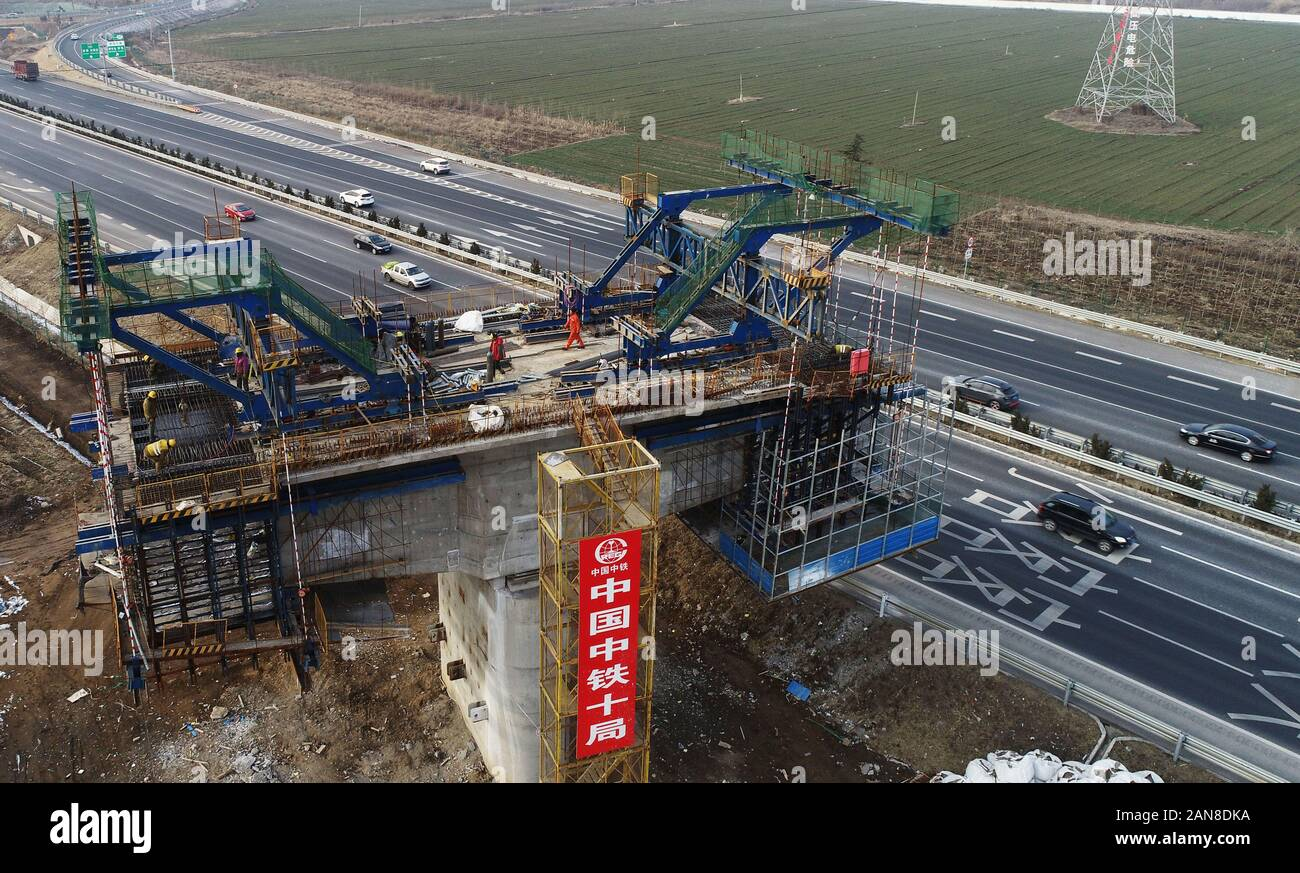 Chinese workers construct piers of a railway over Qingyin (Qingdao-Yinchuan) Expressway in Zouping, Binzhou City, east China's Shandong Province on Ja Stock Photo