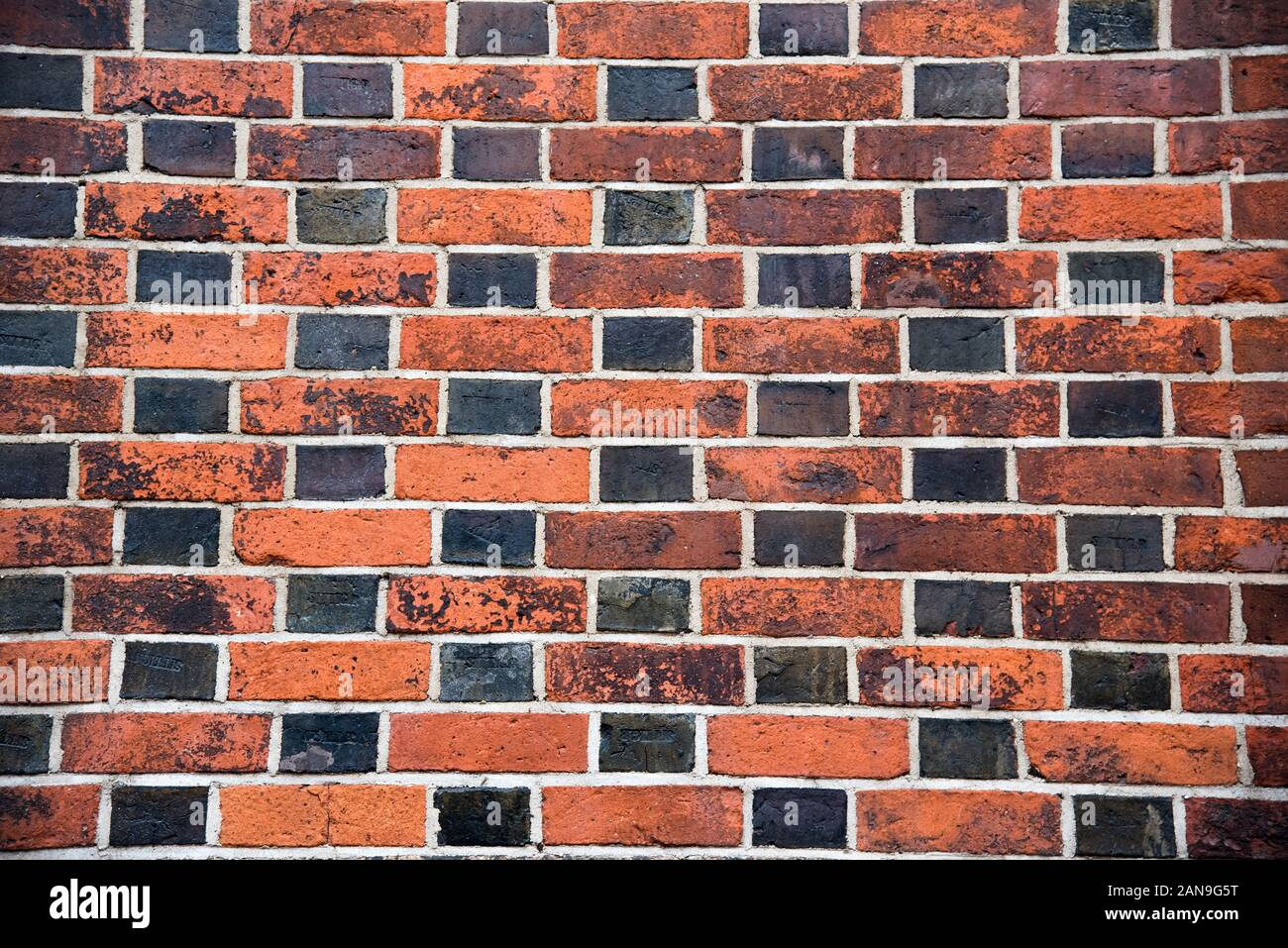 Brick wall background concept with chessboard pattern effect of black and brown bricks shot with wide angle lens Stock Photo
