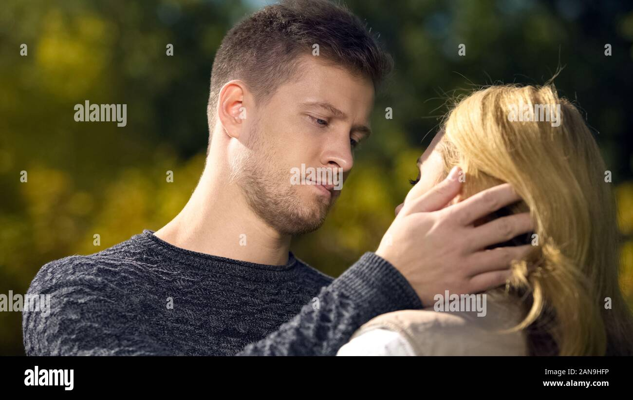 Upset man looking at woman and touching her face, lack of money, unemployment Stock Photo
