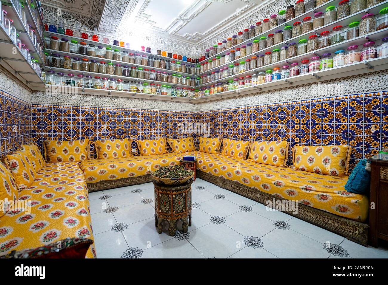 Moroccan interior with variety of spices on shelves and herbal tea in the middle of the room Stock Photo