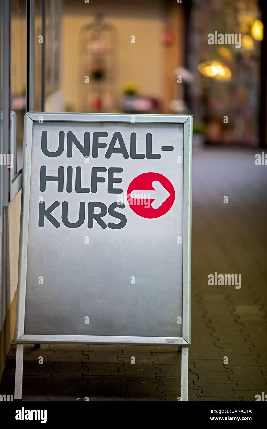 Sign with red arrow pointing the way to the location of the first aid course, text in German language Erste Hilfe Kurs Stock Photo