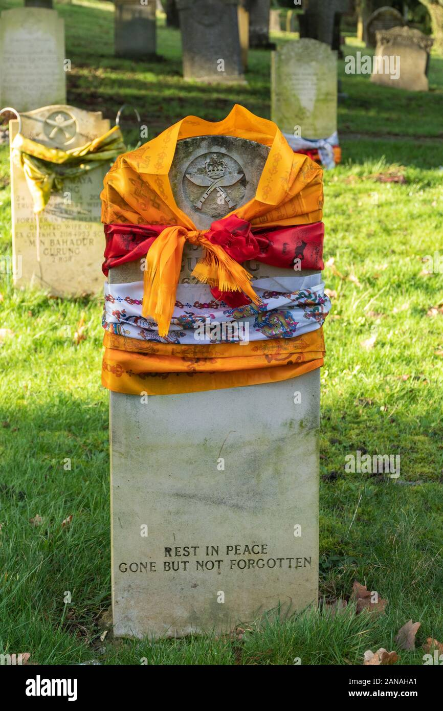 Grave of a Gurkha soldier with the headstone draped with colourful silk scarves, Aldershot Military Cemetery, UK Stock Photo